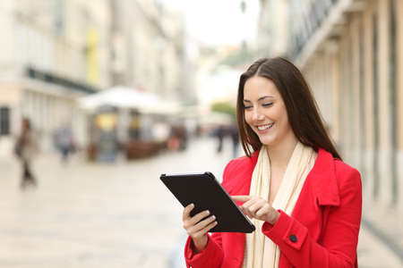 Happy woman uses a tablet in the street of an old town in winter Stock Photo