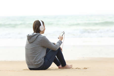 Longing teen alone listening to music sitting on the sand on the beach Banque d'images - 108745184