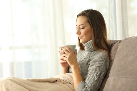 Pensive lady holding a cup of coffee in winter sitting on a couch in the living room at home Stock Photo