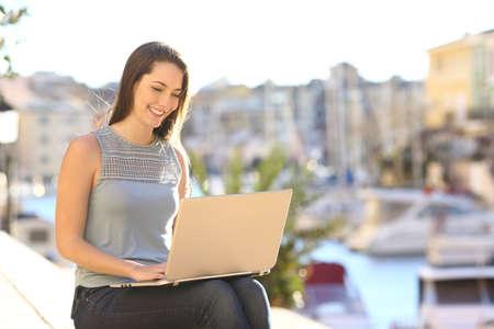 Mujer feliz usando una computadora portátil en una calle soleada de la ciudad costera
