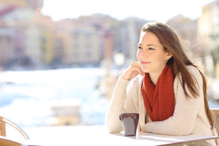 Happy beautiful woman relaxing in a coffee shop on vacation in a sunny day Stock Photo