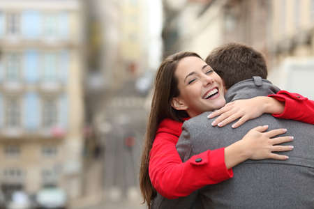 Cheerful couple meeting and hugging in the street with copy space at side