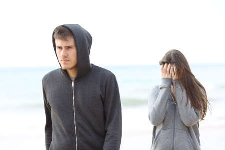 Couple break up on the beach with a man leaving girl alone Stock Photo