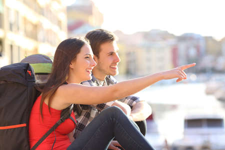 Side view portrait of a couple of backpackers pointing landmark in the street on vacation 스톡 콘텐츠