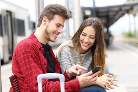 Two happy travelers booking hotel online with a smart phone waiting in a train station