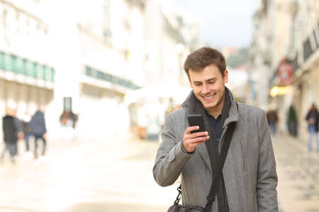 Front view portrait of a happy man walking using a smart phone in winter in the street
