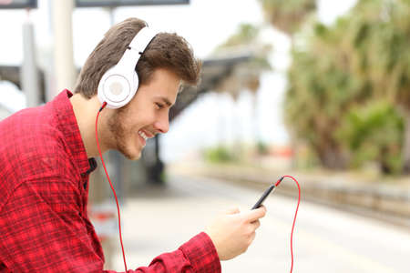 Side view portrait of a happy man listening to music with phone and headphones waiting in a train station