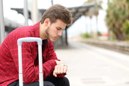 Worried traveler looking at his watch waiting for delayed train Stock Photo