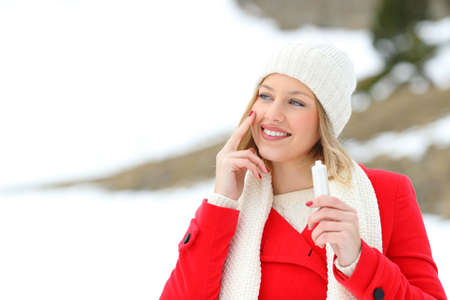 Portrait of a fashion girl in red protecting skin applying moisturizer cream in a snowy mountain in winter holidays