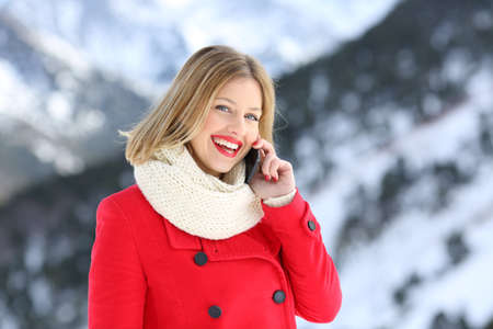Woman talking on phone in winter holiday looking at you in a snowy mountain Stock Photo