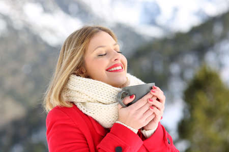 Portrait of a satisfied woman heating holding a coffee mug in winter in a snowy mountain Stockfoto