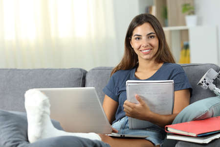 Disabled student stydying and posing sitting on a couch in the living room at home Stock Photo