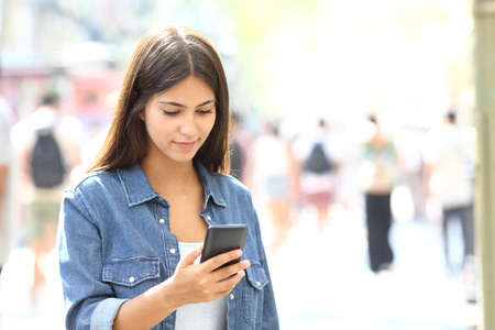 Beautiful relaxed teen using a smart phone walking in the street