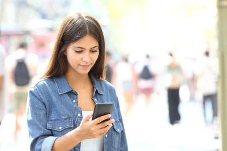 Mooie ontspannen tiener met behulp van een slimme telefoon die in de straat loopt Stockfoto