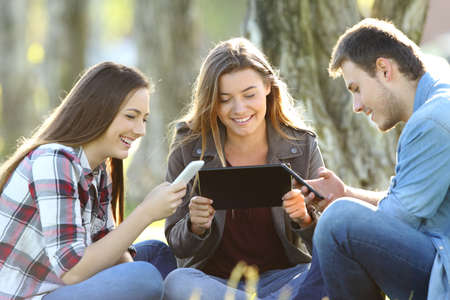 Three happy friends using multiple devices sitting on the grass in a park