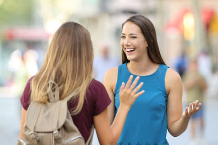 Two happy friends meeting and greeting on the street with a blurred background Stock Photo