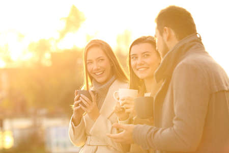 Three happy friends having a casual conversation and drinking coffee at sunset in winter