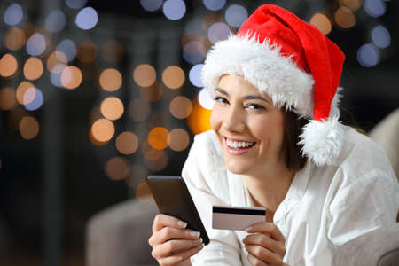 Online buyer looking at you on christmas lying on a couch in the living room at home Stock Photo
