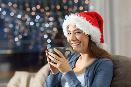 Happy woman holding a cup on chistmas sitting on a couch in the living room at home Stock Photo