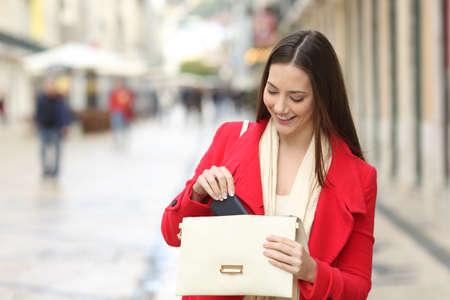 Donna felice in rosso, tirando fuori il telefono dalla borsa in strada in inverno