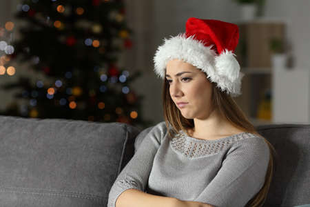 Sad girl in christmas time in the night sitting on a couch in the living room at home Stock Photo - 108937670