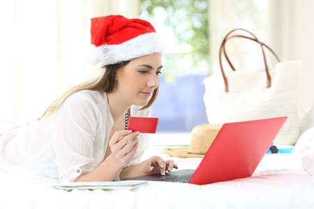 Woman paying on-line on christmas holidays lying on a bed in an hotel room Stock Photo