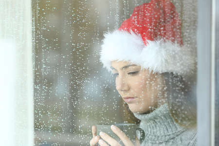 Sad woman in christmas looking down through a windos in a rainy day Stock Photo