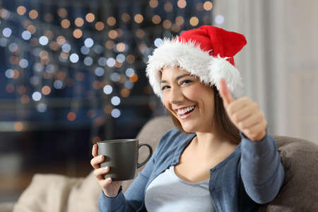 Happy woman with thumbs up on christmas sitting on a couch in the living room at home