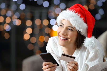 Online buyer thinking on chritmas sitting on a couch in the living room at home