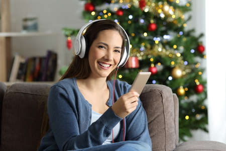 Woman listening to music posing on chritmas sitting on a couch in the living room at home Stock Photo