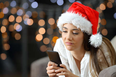 Bored or sad woman checking phone messages in christmas lying on a couch in the living room at home Stock Photo