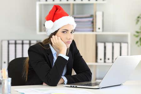 Sad office worker working in christmas time looking at camera