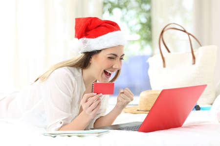 Excited woman buying online on christmas holidays lying on a bed in an hotel room Stock Photo