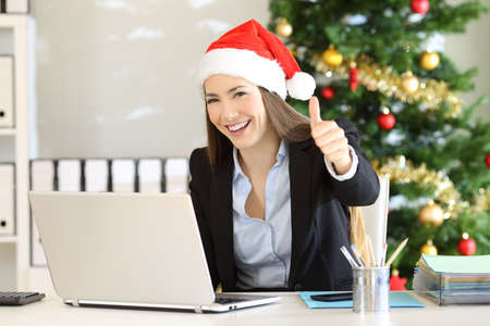 Office worker with thumbs up looking at camera in christmas time Stock Photo - 108938392