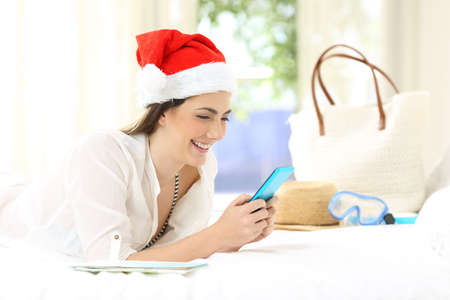 Woman on christmas holidays using a phone lying on a bed in an hotel room Stock Photo