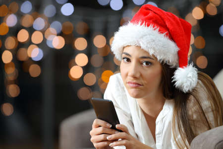 Frustrated woman holding a phone on christmas lying on a couch in the living room at home