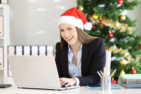 Office employee wearing santa hat posing at workplace in christmas Stock Photo