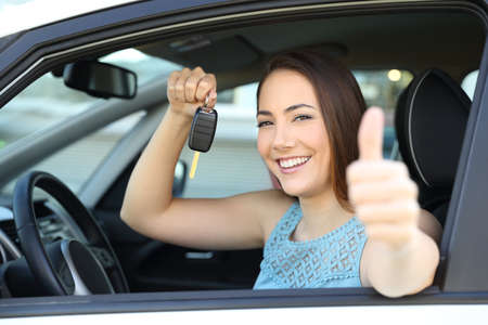 Happy car owner looking at camera holding a key gesturing thumbs up