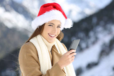 Happy woman holding a smart phone on christmas holidays in the snowy mountain