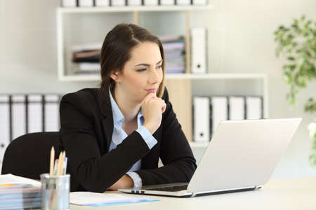 Pensive businesswoman with a laptop looking away at office