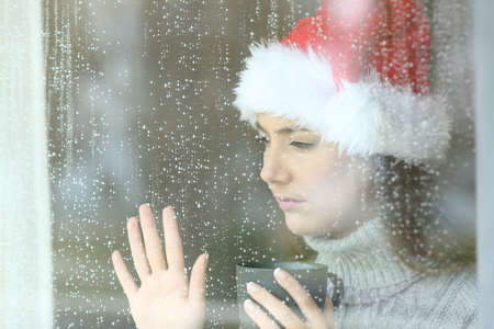 Sad and lonely woman looking through a window touching glass, with the hand in christmas time in a rainy day Stock Photo
