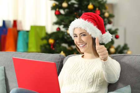 Woman with a laptop and thumbs up on christmas sitting on a couch in the living room at home