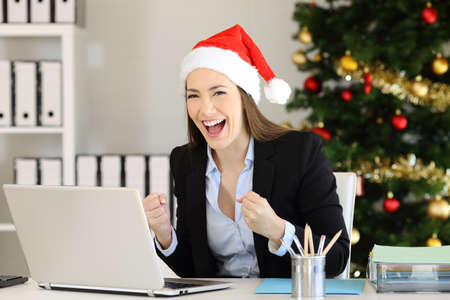 Excited office worker looking at camera in christmas time with a tree in the background