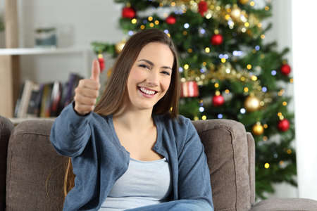 Happy woman in christmas with thumbs up sitting on a couch in the living room at home