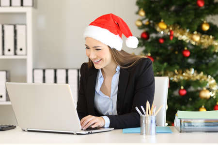 Happy office worker working with a laptop in christmas time