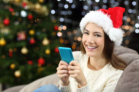 Woman holding smart phone looking at camera in christmas sitting on a couch in the living room at home Stock Photo