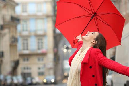 Femme spontanée tenant un parapluie rouge célébrant le succès sous la pluie en hiver