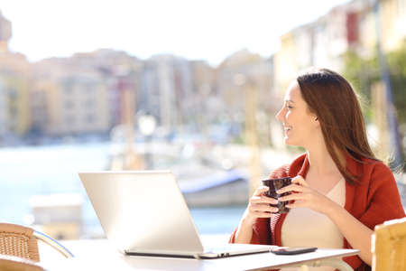 Happy woman with a laptop looking away in a coffee shop on vacation Foto de archivo - 108937451