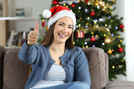 Girl with thumbs up posing on chritmas sitting on a couch in the living room at home
