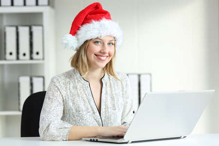 Office worker posing wearing a santa hat looking at camera at workplace